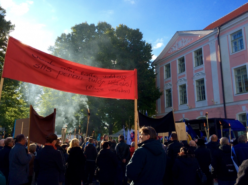 TORCH LIT PROTESTS: Anti-immigrant rally marches past Estonia's parliament, the Riigikogu. (Photo: Helen Wright)